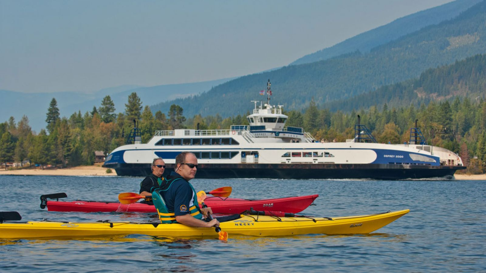 Kayakers alongside the Osprey Ferry on Kootenay Lake at Balfour.